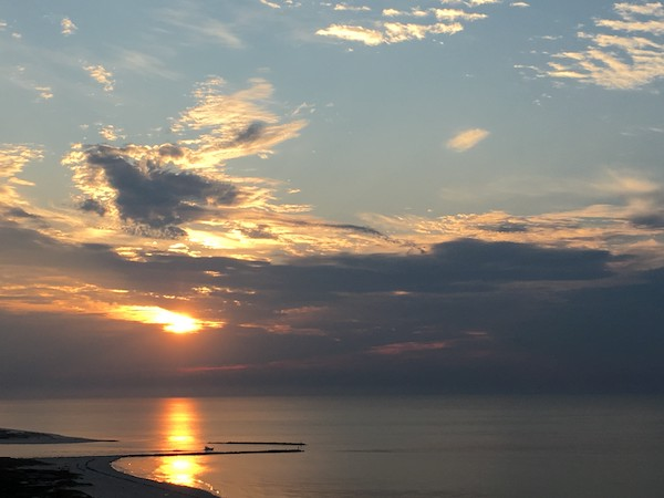 The sun glows orange over the Gulf of Mexico as clouds streak across the sky