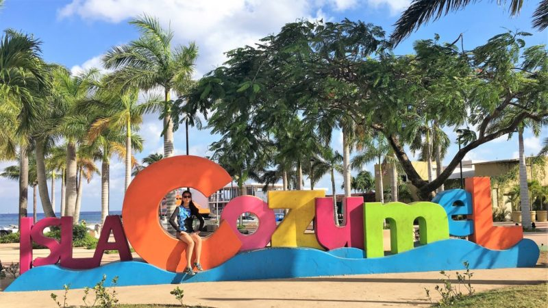Ellie sitting on the Isla Cozumel sign downtown