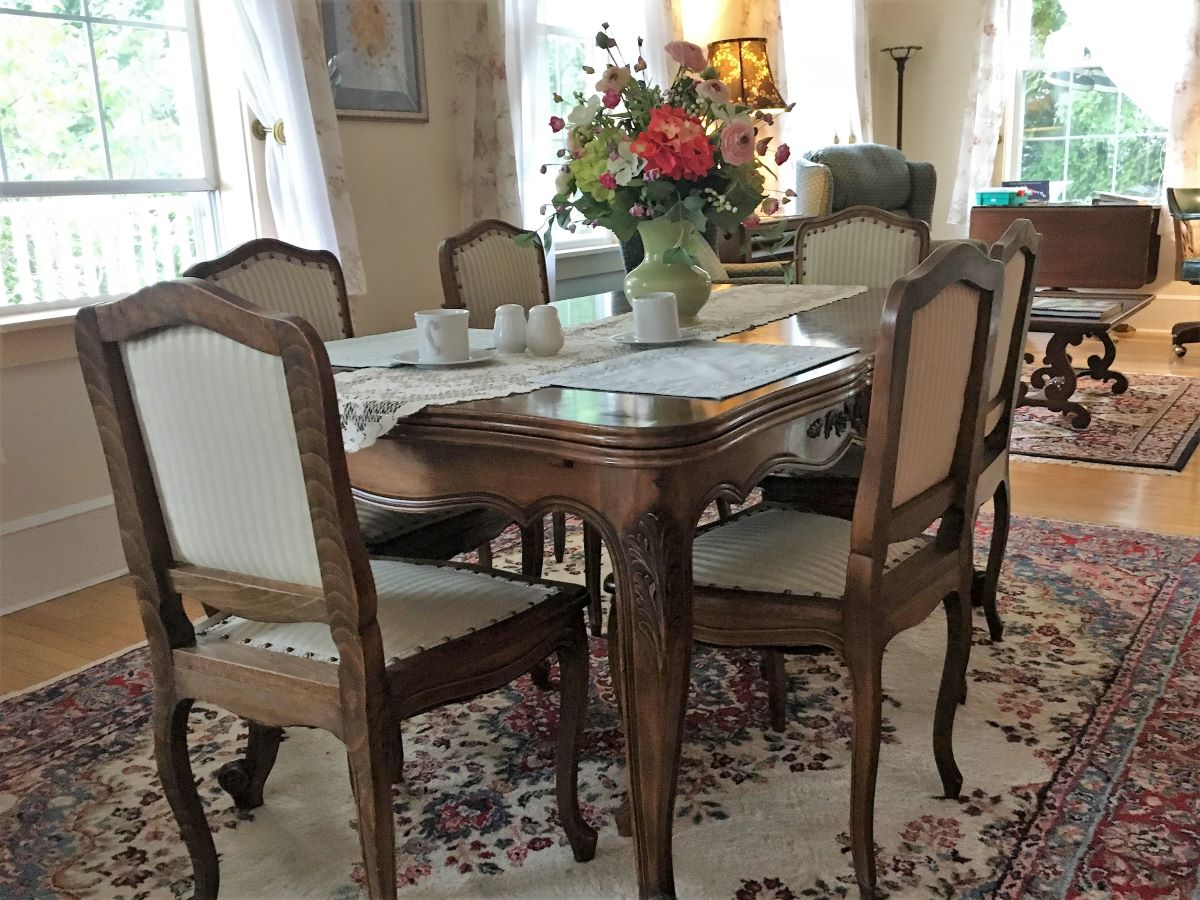 Dining table with six chairs and floral centerpiece
