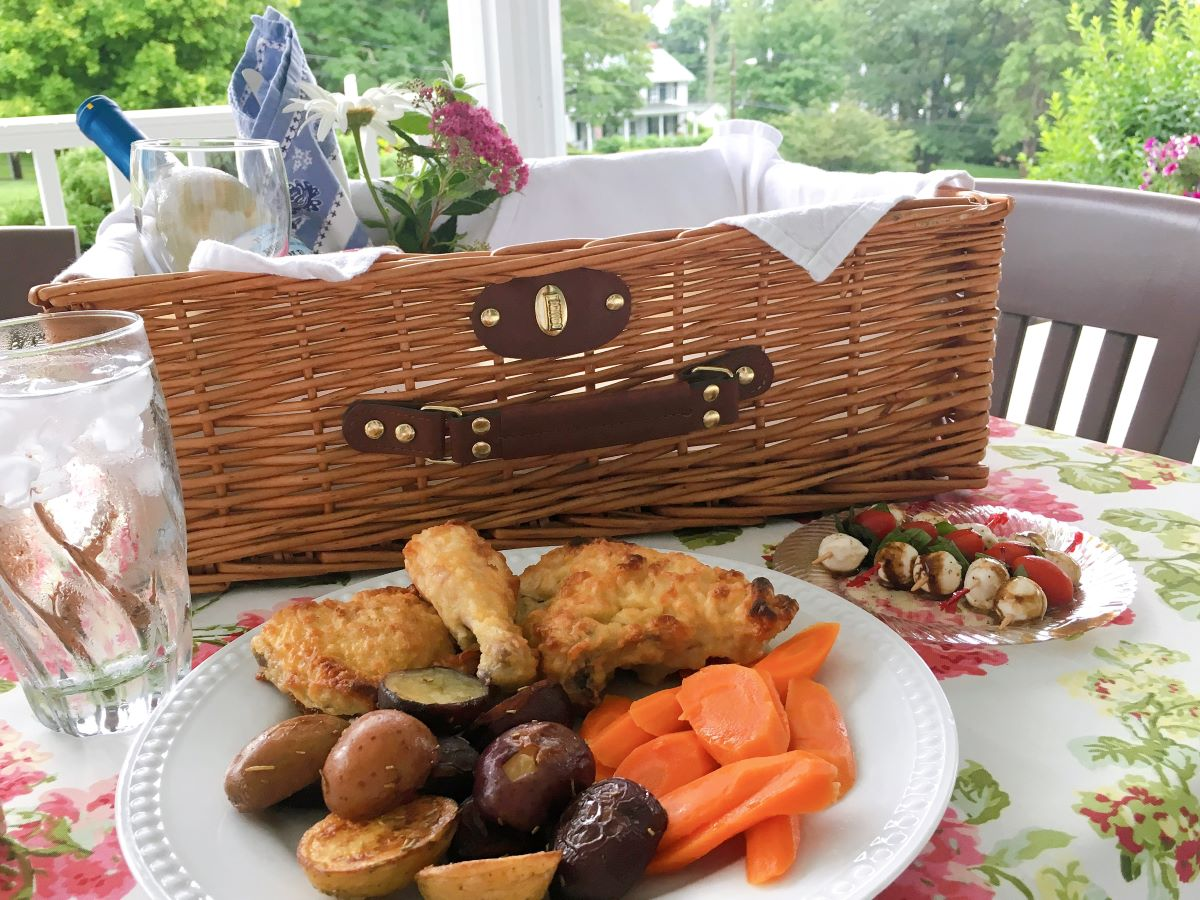 Picnic basket with fried chicken, vegetables, wine and flowers served at a flower covered picnic table.