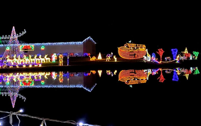 Christmas light display of Santa and Noah's ark reflected on the water.